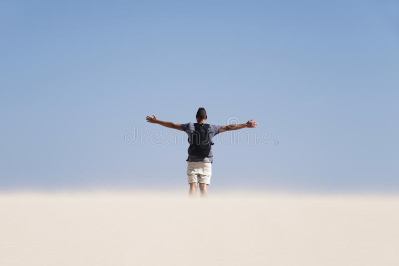 Young man with a backpack in the desert stock photo