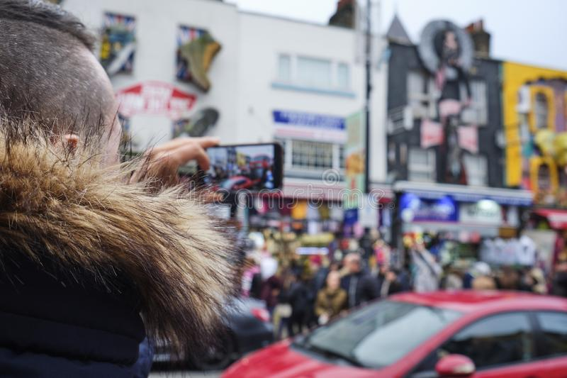 Young man at Camden High Street in London, UK. Closeup of a young caucasian man taking pictures with his smartphone at Camden High Street, in the popular Camden stock images