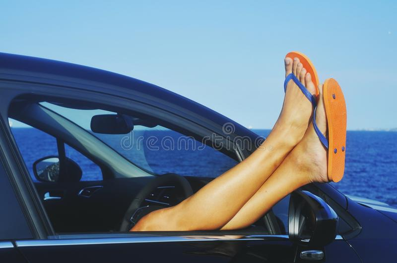 Man relaxing in a car next to the ocean. Closeup of a young caucasian man, wearing a pair of orange flip-flops, relaxing in a car next to the ocean stock photo