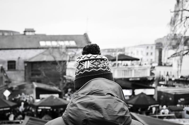 Man at Camden Lock in black and white. Closeup of a young caucasian man, wearing a parka and a knit cap, seen from behind at the popular Camden Lock, in the stock photo