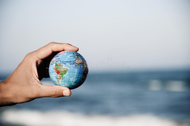 Young man with a world globe in his hand royalty free stock image