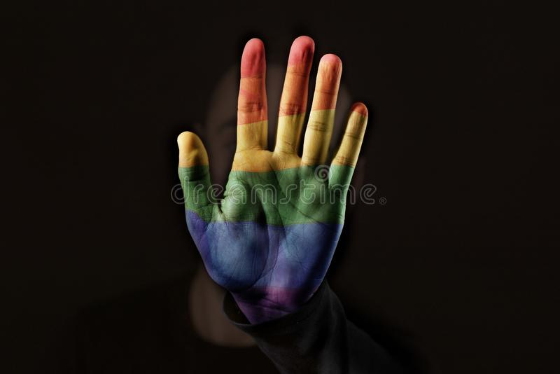 Person with the rainbow flag in his or her hand. Closeup of a young caucasian person with the palm of his or her hand, patterned with a rainbow flag, in front of stock image