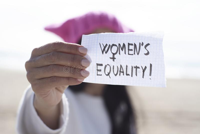 Woman with a pink hat and the text womens equality. Closeup of a young caucasian woman outdoors, wearing a pink pussycat hat, showing a piece of paper in front royalty free stock image