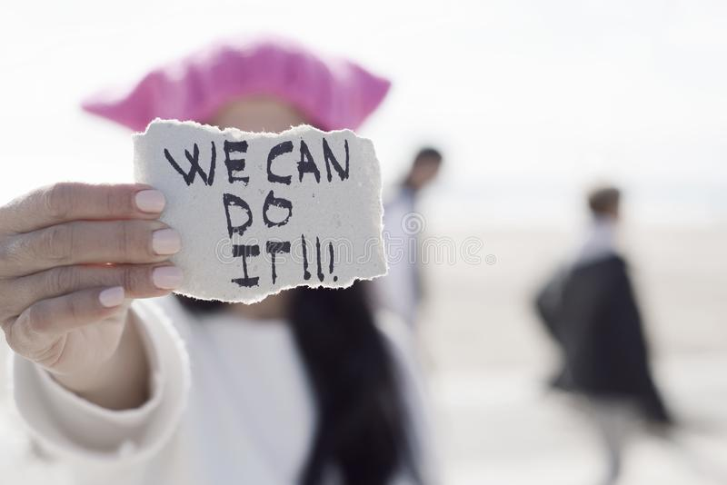 Woman with a pink hat and the text we can do it. Closeup of a young caucasian woman in the street showing a piece of paper with the text we can do it written in stock photography