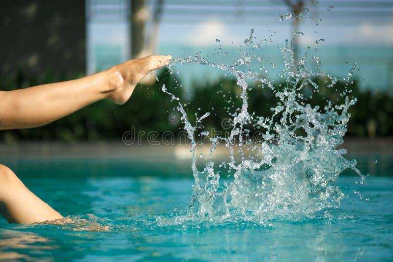 Close up young female leg make splash of blue water in swimming pool. Closeup young female leg make splash of blue water in swimming pool stock photo