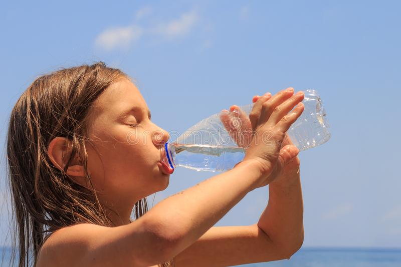 Closeup of young girl drinking fresh cold water from plastic drinking bottle on a hot summer day. stock photos