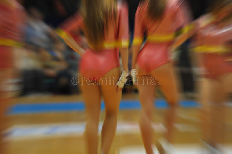 Closeup of a young group of girls cheerleaders performance at competitions, motion blur effect royalty free stock image