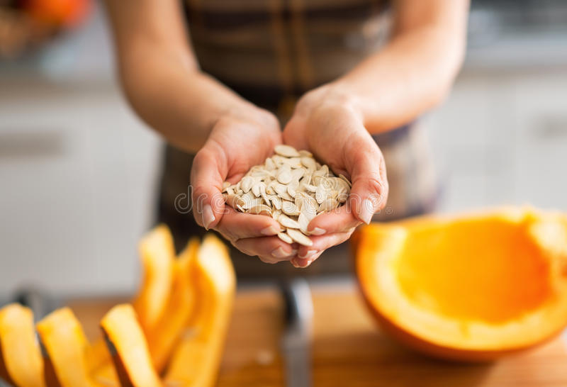 Closeup on young housewife showing pumpkin seeds royalty free stock images
