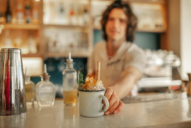 Bartender serving drinks behind the counter of a trendy bar. Closeup of a young male bartender standing behind the counter of a trendy bar serving a colorful royalty free stock photo