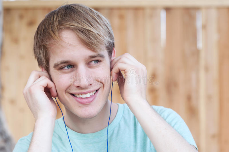 Closeup of young male listening to music stock image