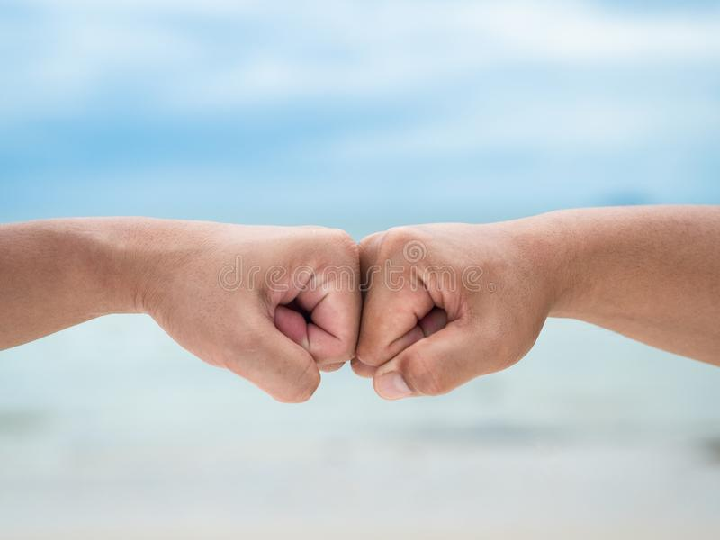 Closeup young man fist bump on the blue sky sea background. Friendship & Teamwork Concept. stock image