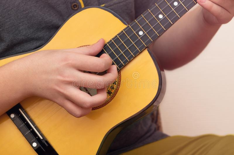Closeup of young man hands playing ukulele royalty free stock image