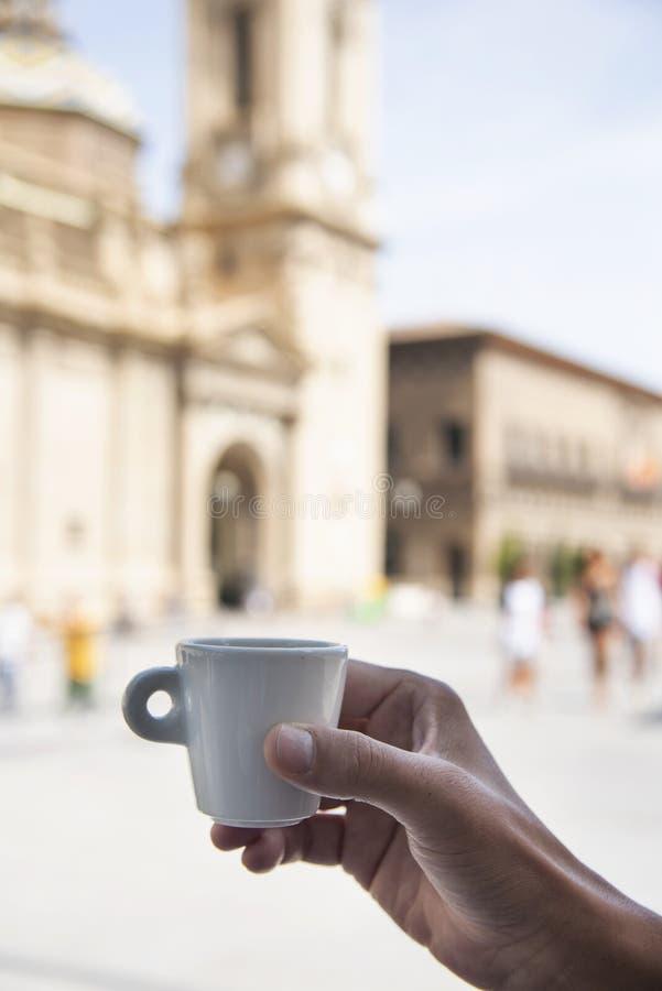 Man having a coffee in Zaragoza, Spain. Closeup of a young man having a coffee in front of the Cathedral-Basilica of Our Lady of the Pillar in Zaragoza, Spain stock photo