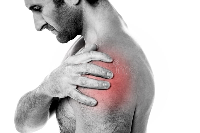 Closeup of young man having pain in shoulder royalty free stock photos