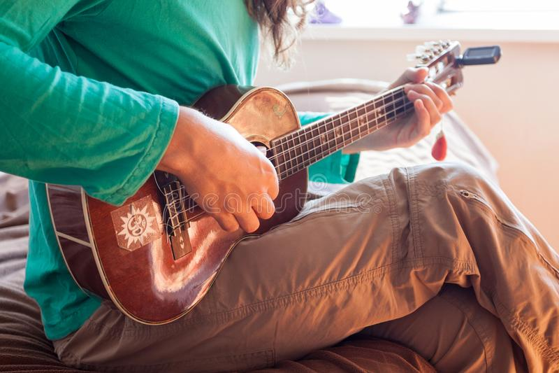 Closeup of a young man`s hands playing an acoustic guitar ukulele at the home. Man holding ukulele. stock image