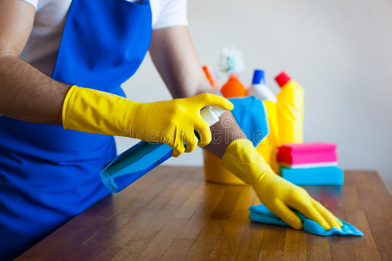 Closeup Of Young Man Wearing Apron Cleaning Kitchen Worktop. Set cleaning concept stock photo