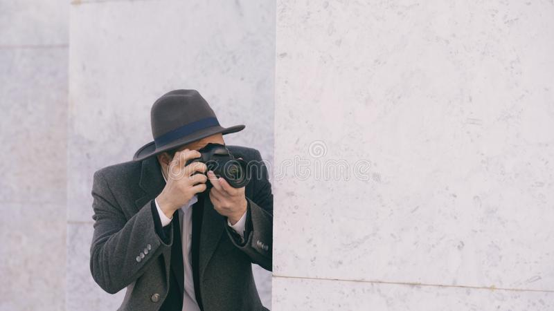 Closeup of young paparazzi man in hat photographing celebrities on camera while spy behind the wall. Closeup of Young paparazzi man in hat photographing stock photography