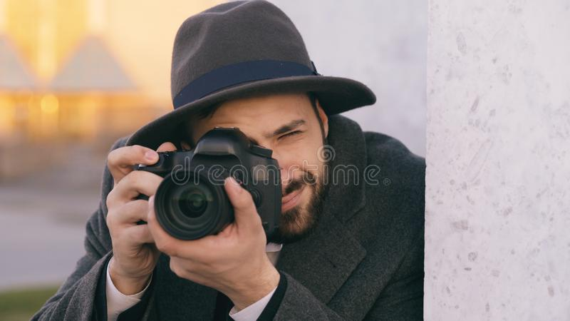 Closeup of young paparazzi man in hat photographing celebrities on camera while spy behind the wall. Closeup of Young paparazzi man in hat photographing stock image