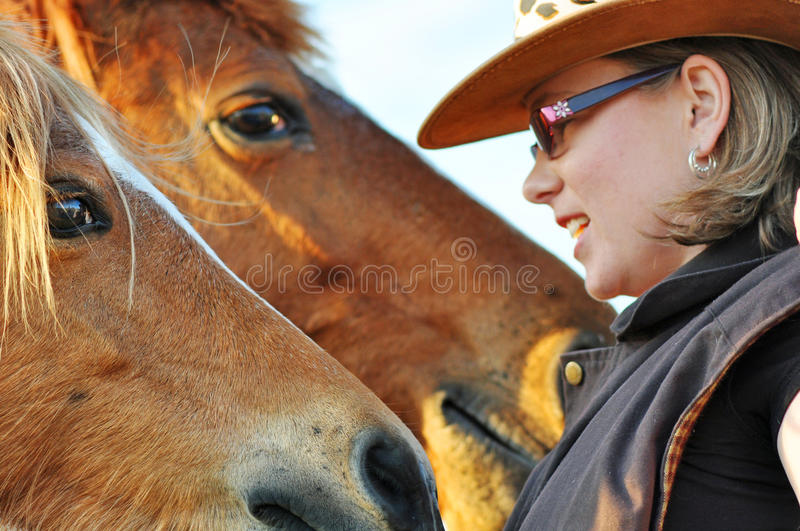 Closeup young pretty woman talking to two horses stock image