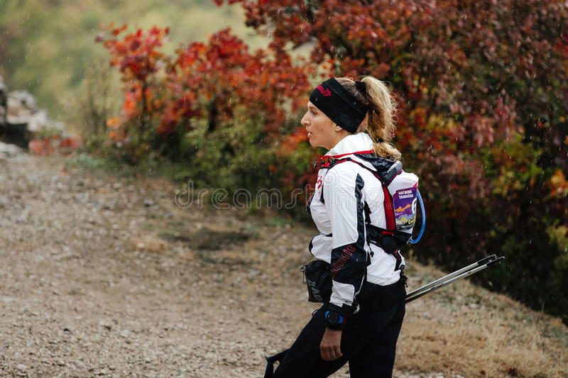 Closeup young runner woman running in rain on a mountain trail with walking poles stock photo