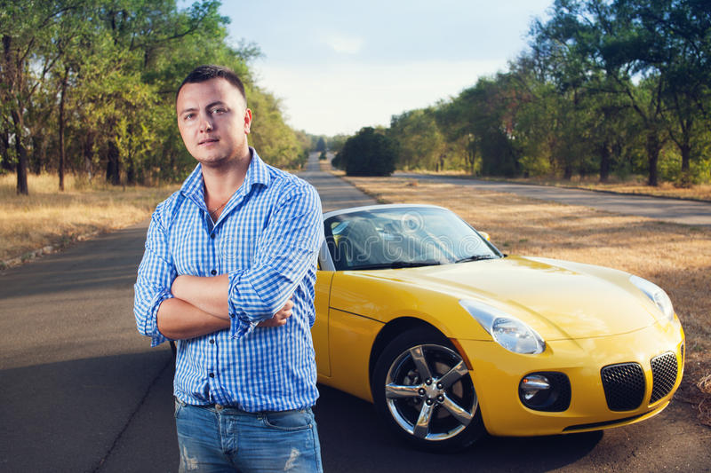 Closeup of young trendy male driver. With his convertible yellow car stock photography