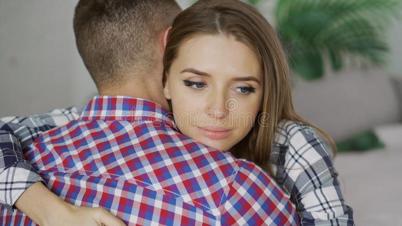 Closeup of young upset couple embrace each other after quarrel. Woman looking wistful and sad hug her boyfrined at home stock photography