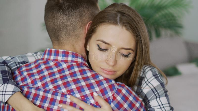 Closeup of young upset couple embrace each other after quarrel. Woman looking wistful and sad hug her boyfrined at home stock photos