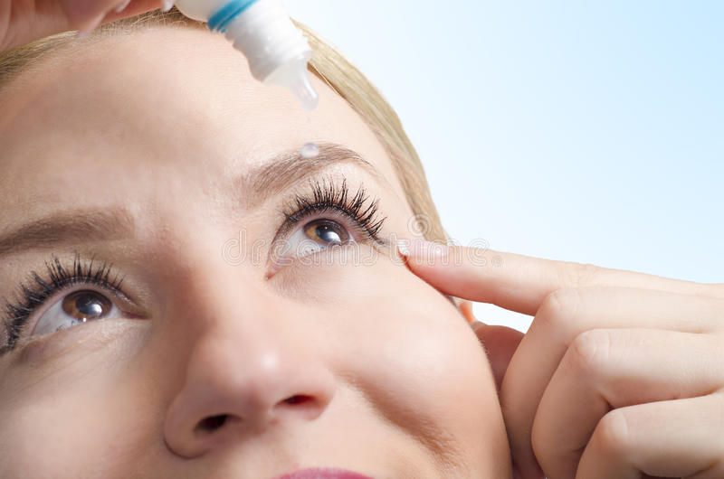 Closeup of young woman applying eye drops. Selective focus only on right eye. Drop captured in mid air/ eye drops with vitamins/ eye care stock photos