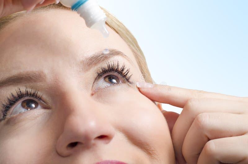 Closeup of young woman applying eye drops stock photos