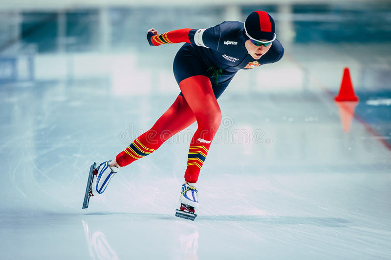 Closeup young woman athlete speedskater goes around turn sprint distance stock photography
