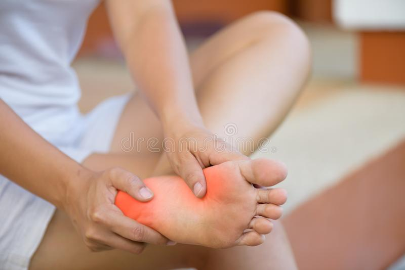 Closeup young woman feeling pain in her foot at home. Healthcare stock image