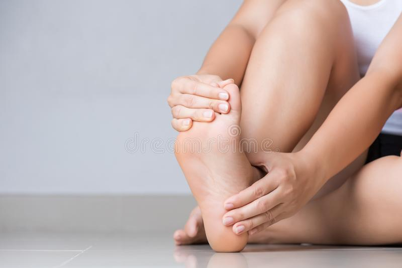 Closeup young woman feeling pain in her foot at home. Healthcare and medical concept stock image
