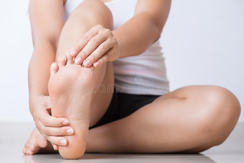 Closeup young woman feeling pain in her foot at home. Healthcare and medical concept stock images