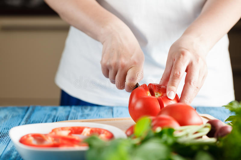 Closeup Of Young Woman In Kitchen Cutting Vegetables royalty free stock photos