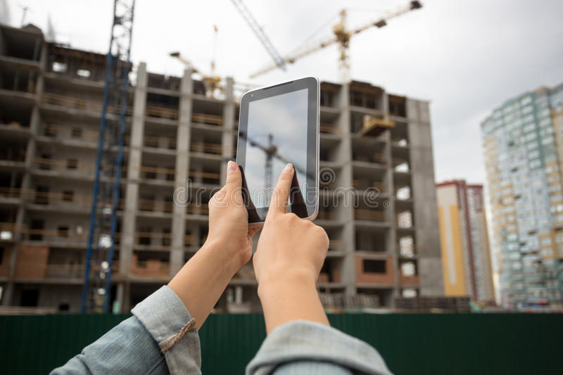 Closeup of young woman posing on building site and using digital stock images