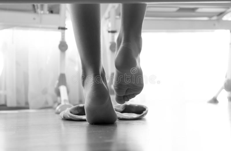 Black and white closeup photo of from under the bed on woman wearing slippers royalty free stock image