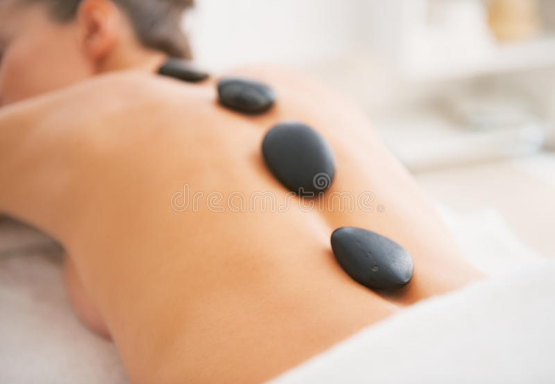 Closeup on young woman receiving hot stone massage. rear view. Closeup on young woman receiving hot stone massage in spa salon. rear view stock photos