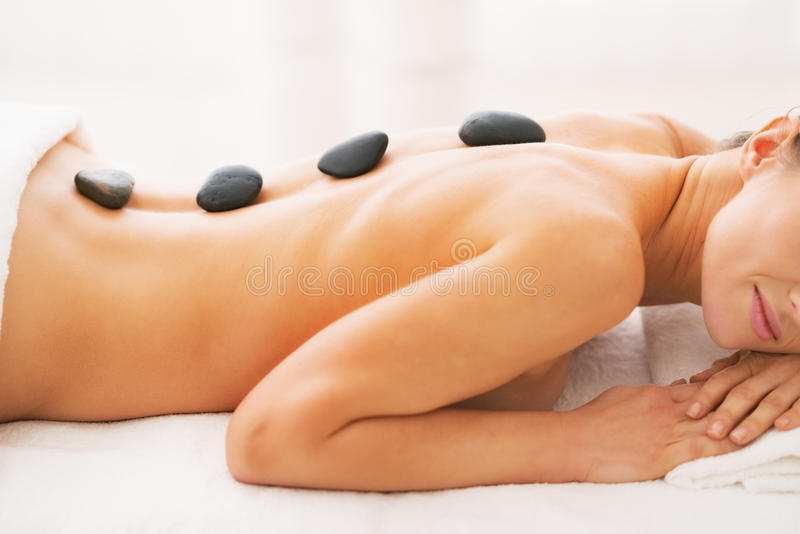 Closeup on young woman receiving hot stone massage. In spa salon royalty free stock images
