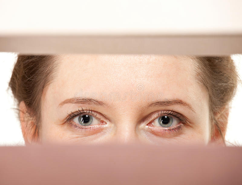 Closeup of young woman's eyes. Watching you closely stock images