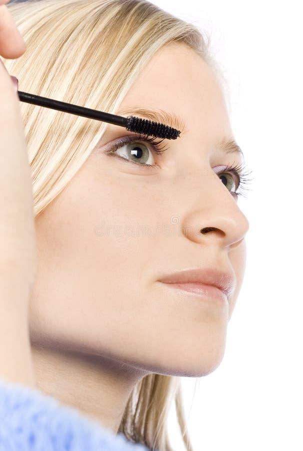 Closeup Of Young Woman's Face Putting Mascara Stock Photos