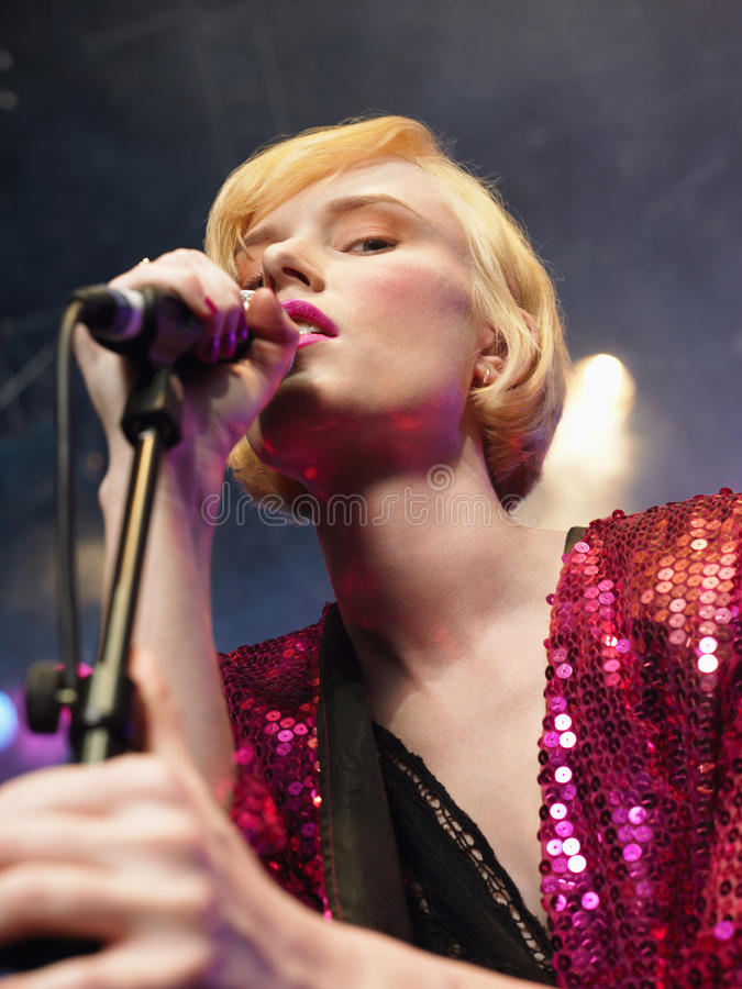 Closeup Of Young Woman Singing Into Microphone royalty free stock images