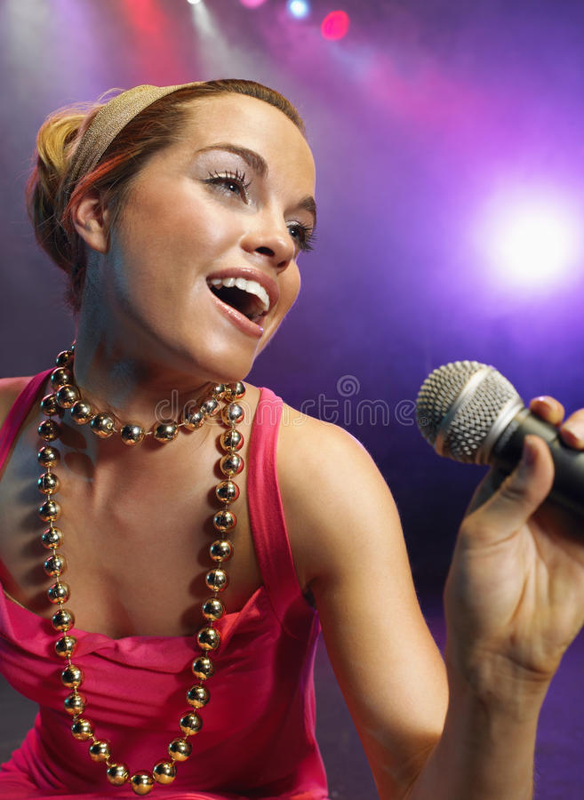 Closeup Of Young Woman Singing Into Microphone stock image
