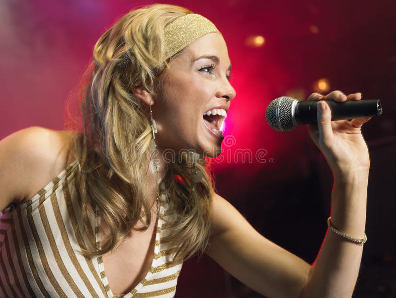 Closeup Of Young Woman Singing Into Microphone royalty free stock photo