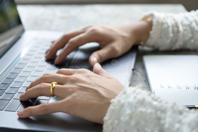 Closeupaffärskvinnan räcker maskinskrivning på bärbar datortangentbordet på skrivbordet arkivbilder
