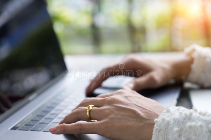 Closeupaffärskvinnan räcker maskinskrivning på bärbar datortangentbordet på skrivbordet arkivfoto