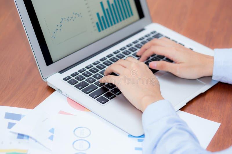 Closeuparbete med finansanalys och hyvladata på bärbara datorn arkivfoto