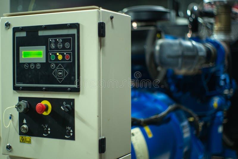 Closeupbelysningindikator på kontrollkabinettet i det elektriska rummet med den suddiga elektriska generatorn i bakgrund fotografering för bildbyråer