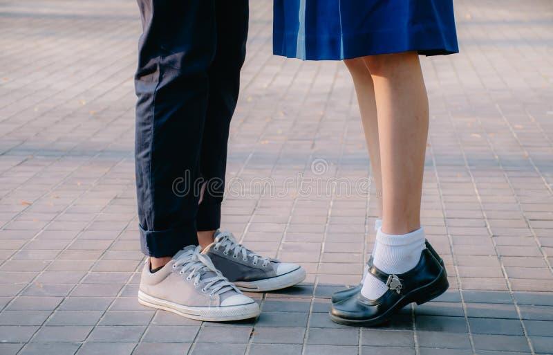 Closeupben och gymnastikskor av unga härliga par i anseende för skolalikformig på gatan parkerar in sommarafton royaltyfria foton