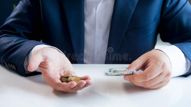 Closeupbild av affärsmansammanträde bak skrivbord- och innehavkreditkort- och metallmynt royaltyfria foton