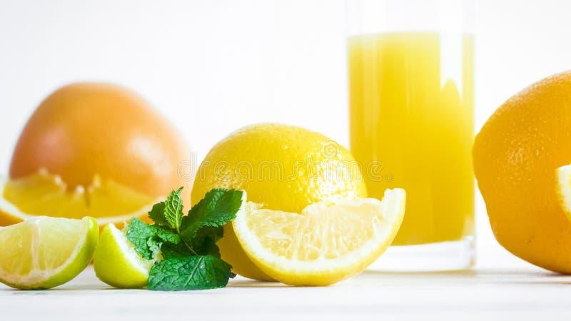 Closeupbild av citroner och apelsiner med exponeringsglas av ny orange fruktsaft på vit bakgrund arkivbilder